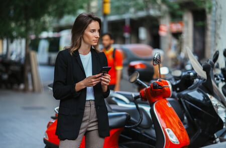 pretty girl in business clothes holds smartphone background of rent mopeds in city of summer street outdoors, active tourist using mobile phone in female hands and plans in online app device walk around busy city scooter