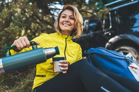 Girl smiles and enjoys breakfast outdoors summer nature, tourist hold mug of warm tea during recreation trip, happy hiker laughing drink coffee from thermos in green forest. Happy tourist relax while traveling auto