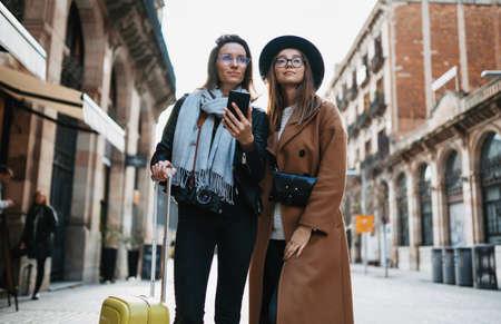Girls plans trip on internet mobile phone, tourist using smartphone, hipster travels in Barcelona. Holiday friendship concept. Travelers hold cellphone, online technology Standard-Bild