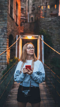 tourist girl blonde with glasses and camera using mobile phone  traveling evening old historical city  Europe, young hipster plans walk through architectural sights of old city and looks at map in cellphone