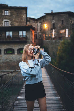 blonde tourist girl stands on suspension bridge walking old historical city and takes photo with retro camera, cute young hipster enjoying a weekend vacation in summer uses photocamera to take picture of her journey