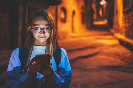 portrait tourist girl using mobile phone with eyeglasses reflection of screen light backdrop of street old historical city at night, young woman traveler plans walk through architectural sights of old town looks at online map in smartphone