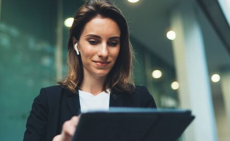 Pensive female student of faculty of law checking mail and reading notification with financial news on tablet device standing outdoors near evening neon lights