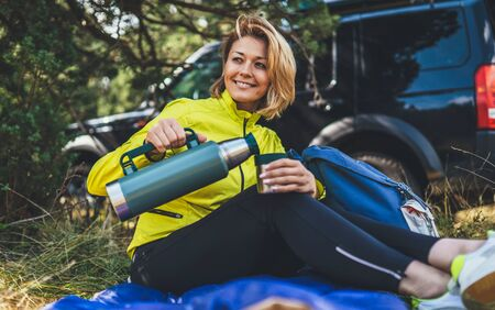 Girl smiles and enjoys summer nature hold hand mug of warm tea during recreation picnic outdoor, hiker laughing drink coffee from thermos in green forest. Happy tourist relax while traveling auto trip Foto de archivo