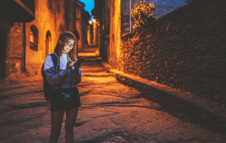 tourist girl blonde with glasses and camera using mobile phone  traveling in night old historical city Europe, young hipster plans walk through architectural sights of old city and chats in cellphone