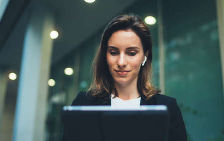 Successful female banker using tablet and wireless earphones outdoors near his office background lights, portrait young woman professional manager working on pc computer evening city Standard-Bild