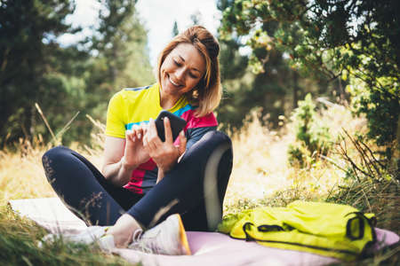 Isolation girl laughing using smartphone after training in park. Smile woman relax after exercising sport outdoors, healthy lifestyle concept.  joy blogger Internet communication online wi-fi mobile phone on nature