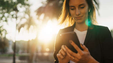successful business woman texting on smartphone working in park barcelona sun day, Young professional finance girl using mobile device on background sun flare outdoors
