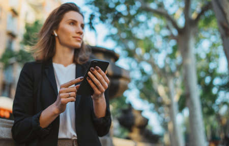 young  businesswoman writes messages on smartphone while walking in a Barcelona Park on Sunny day, cheerful professional financier girl uses mobile device on background trees outdoors Standard-Bild