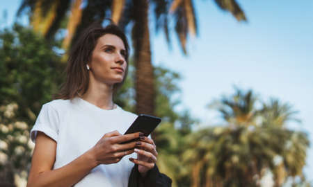 pretty woman reads  text message on mobile smartphone while standing in a Park on a warm summer day, gorgeous woman listens to music on earphones and searches for information on cell phone Standard-Bild