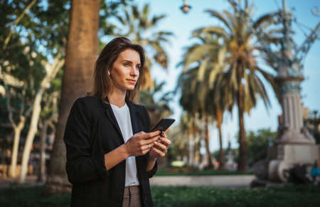 elegant girl in suit holds a smartphone in hand and looks into distance while walking in a Park in Barcelona, girl мanager checks chat with colleagues on mobile phone after office work