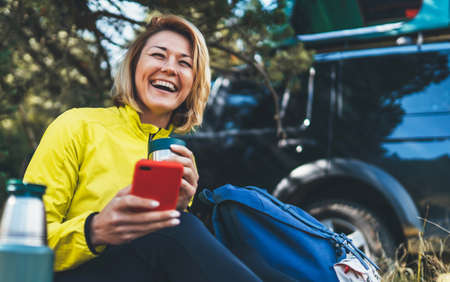 Happy auto tourist laughing talking on cellphone drinks tea while traveling. Young woman smile showing teeth calling on internet mobile phone summer green forest. Joy girl using smartphone have fun emotion in outdoors
