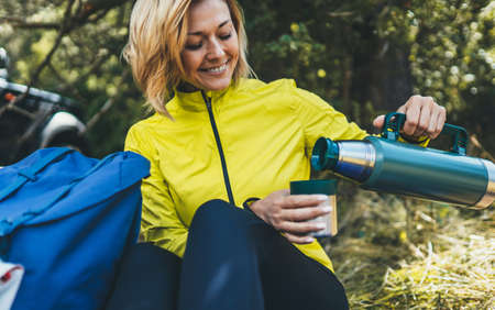 Girl smiles and enjoys breakfast outdoors summer nature, tourist hold hand mug of warm tea during recreation trip, happy hiker drink coffee from thermos in green forest,  tourist relax while traveling