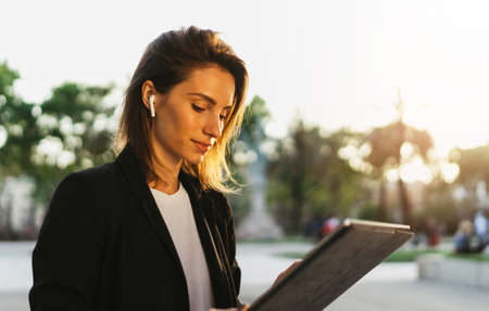 Successful business woman using tablet and wireless headphones walking city street, girl communicates conference call with office colleagues outdoors, Portrait young Manager working on PC computer background sunset in park Standard-Bild