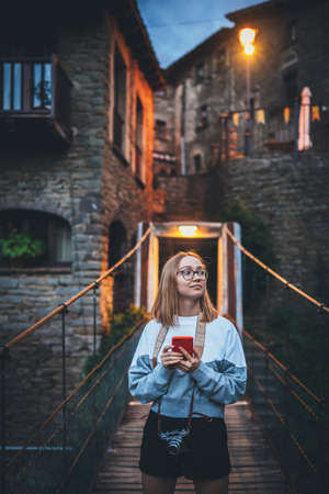 tourist girl with camera stands on suspension bridge of old historical city uses smartphone to plan walk outdoor, cute blonde hipster holding mobile phone enjoying weekend vacation in summer evening