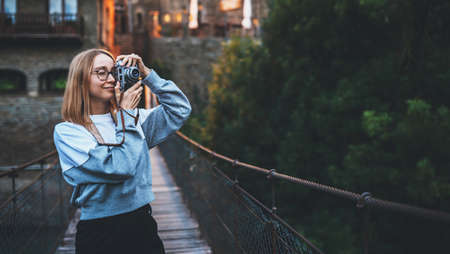 blonde tourist girl with glasses stands on suspension bridge of old historical city and takes photo with retro camera, cute young hipster enjoying a weekend vacation in summer uses photocamera to take picture of her journey
