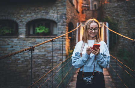 tourist girl blonde with glasses and camera stands on suspension bridge of old historical city uses smartphone to plan walk, cute young hipster looks at  mobile phone screen enjoying weekend vacation in summer Standard-Bild