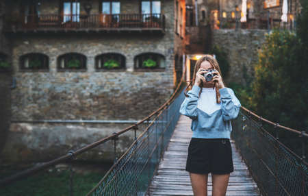 tourist girl stands on suspension bridge walking old historical city and takes photo with retro camera, cute young hipster woman enjoys weekend vacation in summer uses camera takes photos on background evening historical architecture