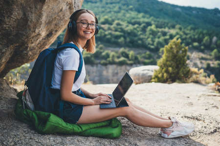 fun tourist girl with glasses and headphones using digital tablet device relax in nature outdoor, hipster woman with backpack listen music and laptop computer on backdrop of high mountains Standard-Bild