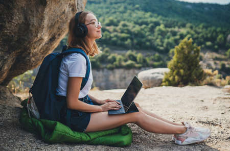 blonde girl after walk in mountains rests listening to music in headphones typing on a laptop in nature, traveler woman plans route in digital tablet looks at online map for walk