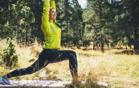 Smile fitness girl exercising yoga outdoors in park, activity pose with stretch legs, sporty woman stretching exercises training outside. Sportswoman isolaition in nature