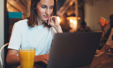young female manager using laptop in cafe interior, hipster girl freelancer looking on computer monitor, businesswoman working via portable computer, woman online learning in restaurant, internet communication concept Standard-Bild