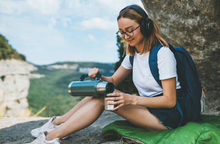 girl traveler listen music with headphones and drinks tea from flask while sitting in mountains in fresh air, tourist with glasses rests in nature drinks coffee in nature outdoor Standard-Bild