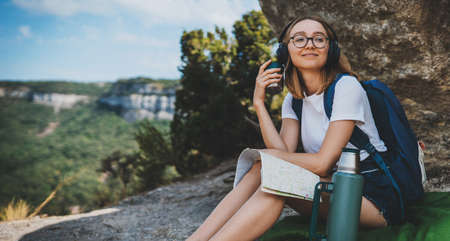 young girl traveling in mountains planning route on map and drinking tea from flask enjoying the trip, female student tourist with glasses relaxing in nature vacation listening music with headphones, copy space for text