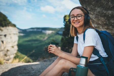 tourist girl in short shorts rest after walking on mountains and drinking tea or coffee outdoor,  active female traveler in glasses and backpack relaxing in nature and listening music with headphones, copy space for text