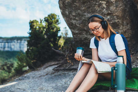 hiker girl with backpack and �up of drink in her hand looks at map sitting in mountains and plans trip route, female person in glasses planning hiking while listening to music in wireless headphones and relaxing during journey