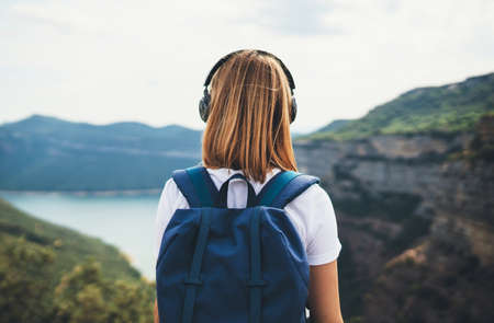 view from behind girl backpacker with blonde hair listening to music headphones standing peak in rocky mountains, traveler with backpack looks into distance enjoying view river valley, copy space