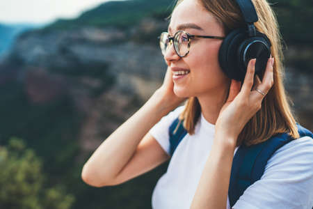 beautiful young traveler with long blonde hair and hipster glasses rests and listens favorite music in wireless headphones smiles while enjoying a hike trip through natural mountain landscape on vacation