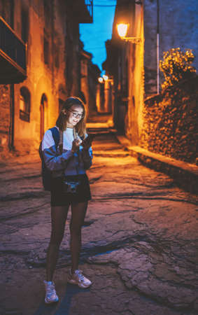 tourist girl blonde with glasses and camera chats in mobile phone  traveling evening old historical city Europe, young woman plans walk through architectural sights of old city and looks at map in smartphone Standard-Bild