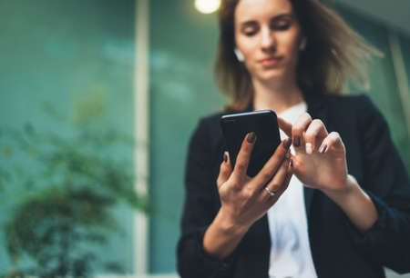 Close-up of female hands holding a smartphone  on the street, focused businesswoman in a black suit and using a modern smartphone near office in early morning Standard-Bild