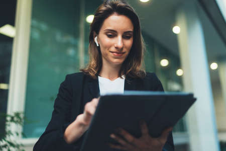 Successful female banker using tablet and wireless earphones outdoors near his office background lights, portrait young woman professional manager working on touch pad near skyscraper in evening city Standard-Bild