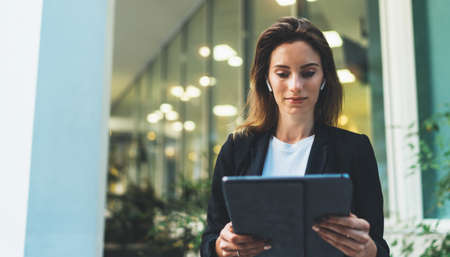 Successful female banker using tablet and wireless earphones outdoors near his office background lights, portrait young woman professional manager working on touch pad in evening city Standard-Bild