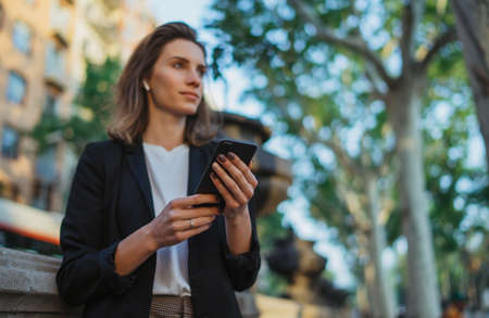 portrait elegant woman with smartphone in street city. Happy businesswoman is using phone outdoors. Cheerful business woman in  jacket with cell phone in park Standard-Bild