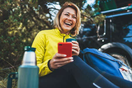 Happy tourist laughing talking on cellphone drinks tea while traveling auto. Young woman smile showing teeth calling on internet mobile phone summer green forest. Isolation fun girl using smartphone outdoors Reklamní fotografie