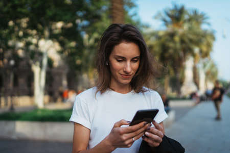 Beautiful young stylish woman walking  streets using modern smartpone, hipster female blogger typing text message on her cellphone in park
