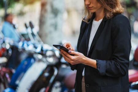 modern woman in business suit holding in hands smartphone uses app scooter rental service outside in city,  female manager looks at map on her mobile phone to rent scooter for quick trip to office, �oncept of urban transport