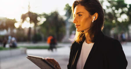 successful female banker using tablet and wireless headphones communicates via conference call with colleagues outdoors, Portrait young woman professional Manager working on a PC computer background sunset in park Standard-Bild