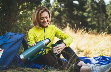 Girl smiles drink coffee from flask on nature after training, woman hold hand mug of warm tea during recreation trip, hiker laughing enjoys breakfast outdoors in green forest. Tourist relax while traveling