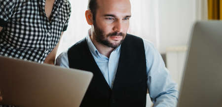 Bearded businessman working at office. colleague discuss project, director looking in monitor computer. Managers meeting marketing plans. Workplace teamwork concept