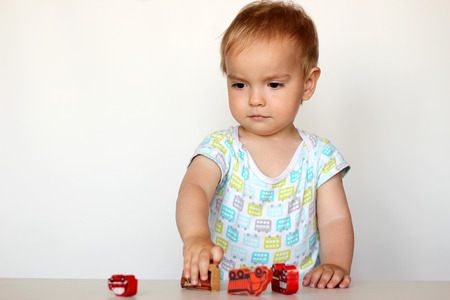 toddler boy: Cute toddler boy playing with wooden toy cars and imagining an accident on white background, safety and traffic regulations Stock Photo