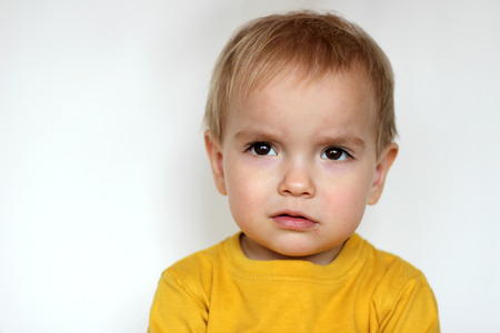 Handsome rapturous small toddler boy in yellow T-shirt with dissatisfied face over white background, face emotions concept, indoor close-up