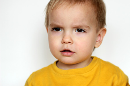 Close-up portrait of handsome toddler boy with interested emotion on his face, indoor portrait
