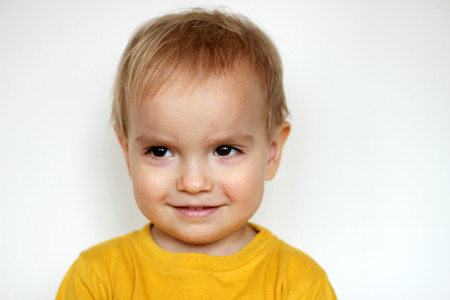 sincerely: Handsome rapturous small toddler boy in yellow T-shirt smiling sincerely and shied over white background, face emotions concept, indoor close-up