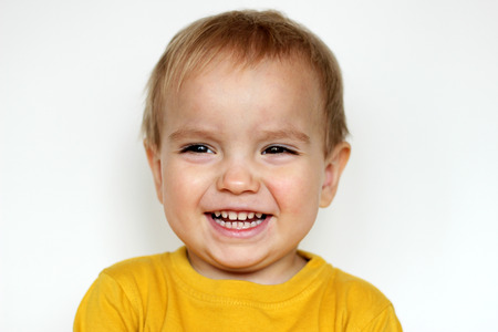 sincerely: Handsome happy small toddler boy in yellow T-shirt smiling sincerely over white background, face emotions concept, indoor close-up
