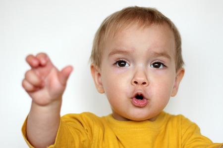 Stattliche verzückten kleinen Kind Junge im gelben T-Shirt mit dem Gesicht wie er ein Lied mit Begeisterung über weißem Hintergrund singt, das Gesicht Emotionen Konzept, Indoor-close-up
