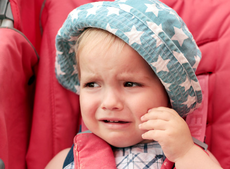 painfully: Crying baby boy wearing a summer hat in the stroller, bad mood, negative emotion concept